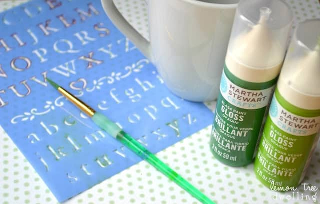 art supplies - stencils, paint brushes, and a white coffee mug to decorate