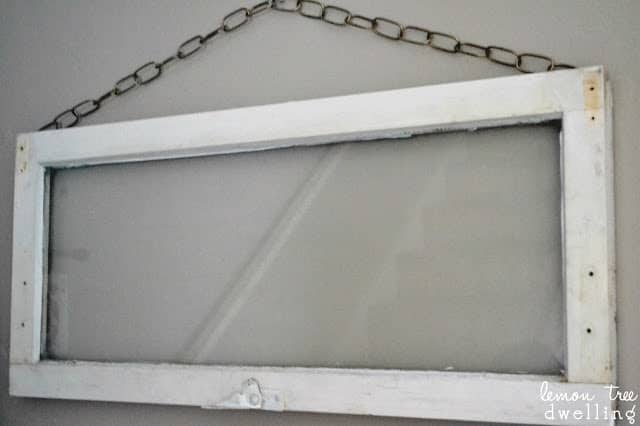 an old white window hanging on a wall with chain