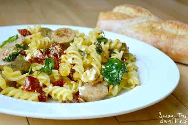 white dinner plate with sundried tomato pasta and a loaf of French bread next to it