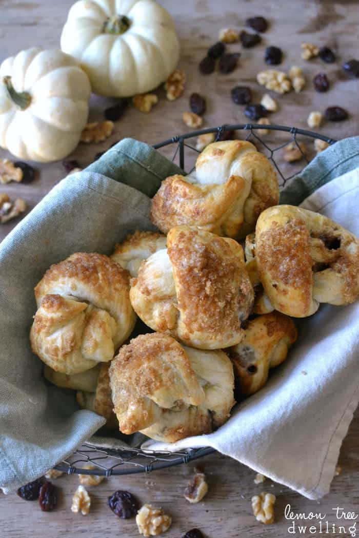 Cranberry Walnut Knots made with Rhodes Dinner Rolls are easy to make and are sure to please everyone. These delicious little rolls are stuffed with dried cranberries and walnuts and topped with a brown sugar streusel to add a little sweetness to your Thanksgiving table!