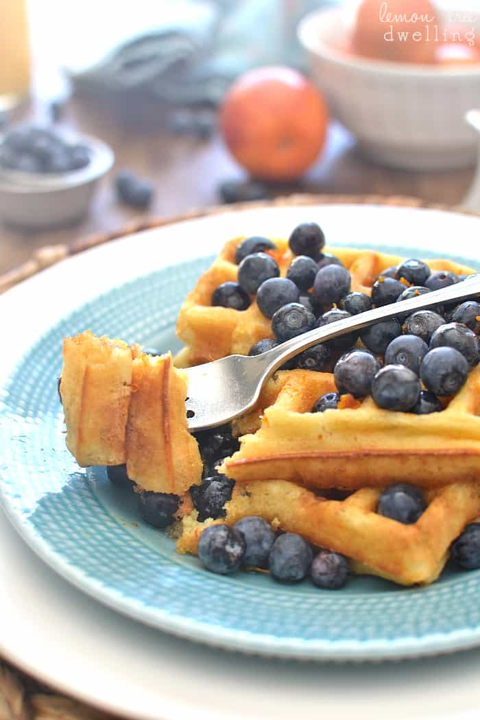 Blueberry Orange Waffles - flavored with orange juice and fresh orange zest and topped with warm vanilla maple syrup. YUM!