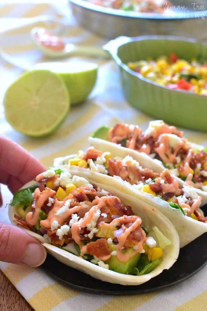 Bacon Avocado Taco Boats - loaded with lettuce, bacon, avocado, cheese, fresh corn salsa, and spicy sriracha mayo. My family LOVED these!