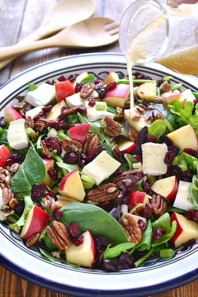 Dressing pouring on Apple Brie Salad