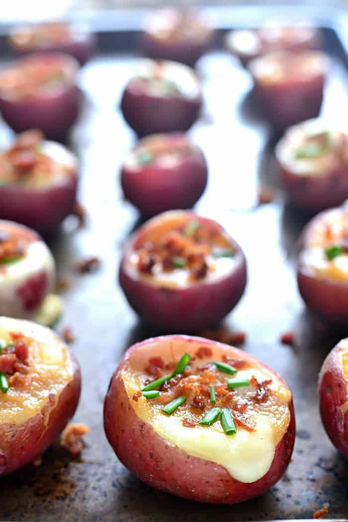 These Poutine Potato Poppers combine all the flavors of poutine in one delicious bite! Bursting with fresh cheese curds and gravy and topped with crispy bacon and chives, these little poppers are the perfect appetizer or mini meal!