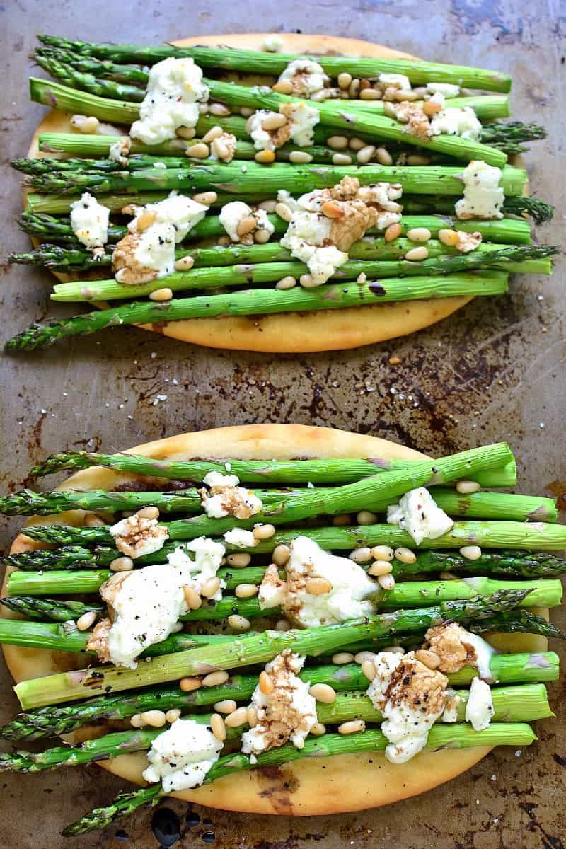 2 grilled flatbreads topped with goat cheese and stalks of fresh asparagus