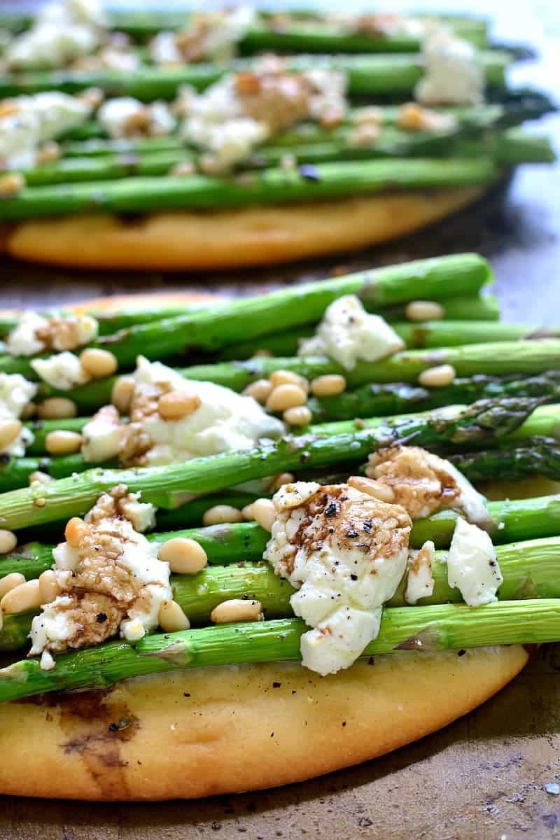 close up image of vegetarian flatbread topped with asparagus, goat cheese, and pine nuts