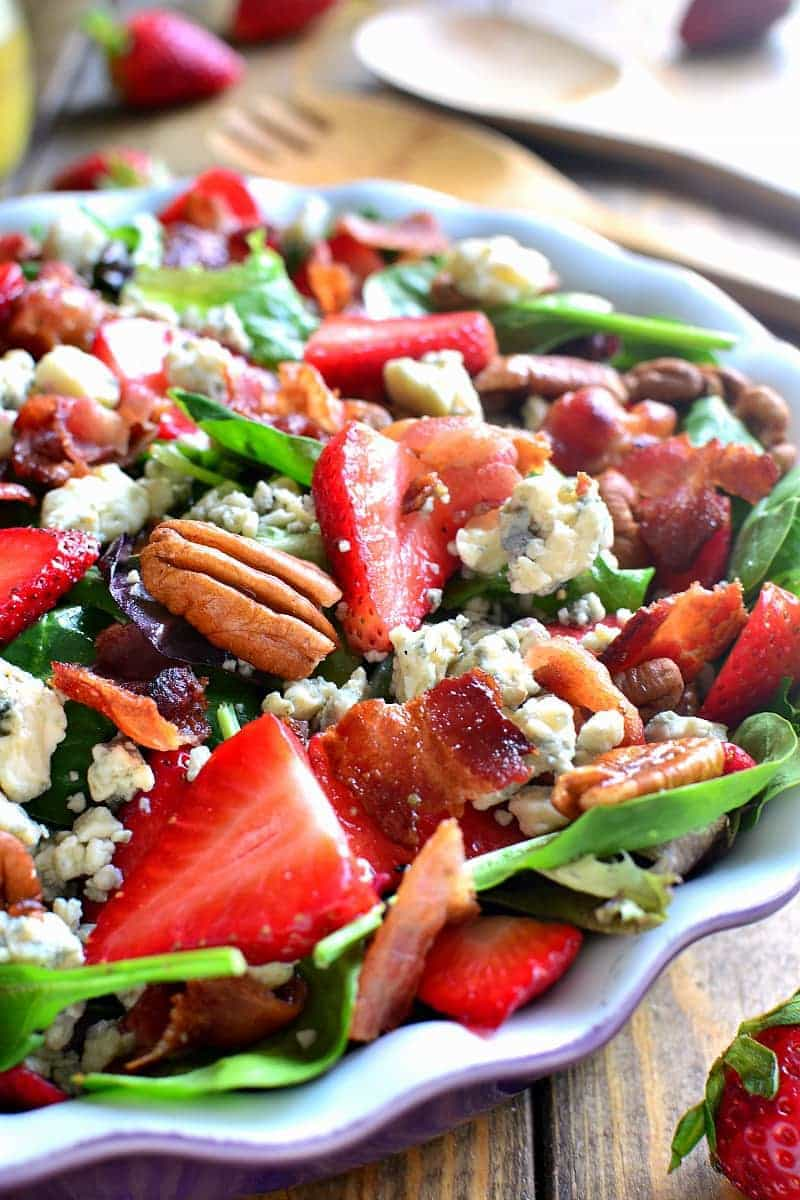 close up image of a summer salad with fresh strawberries, pecans, bacon, and crumbled blue cheese