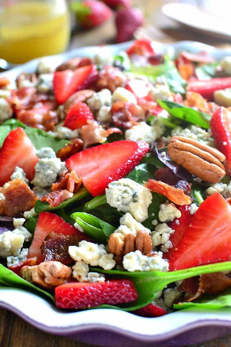 a bowl of summer salad with strawberries, bacon, and blue cheese