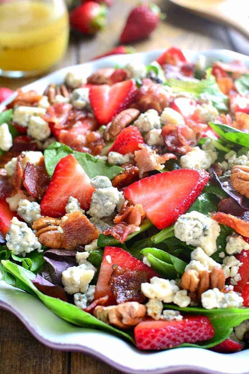 a scalloped bowl filled with Strawberry Bacon Blue Cheese Salad