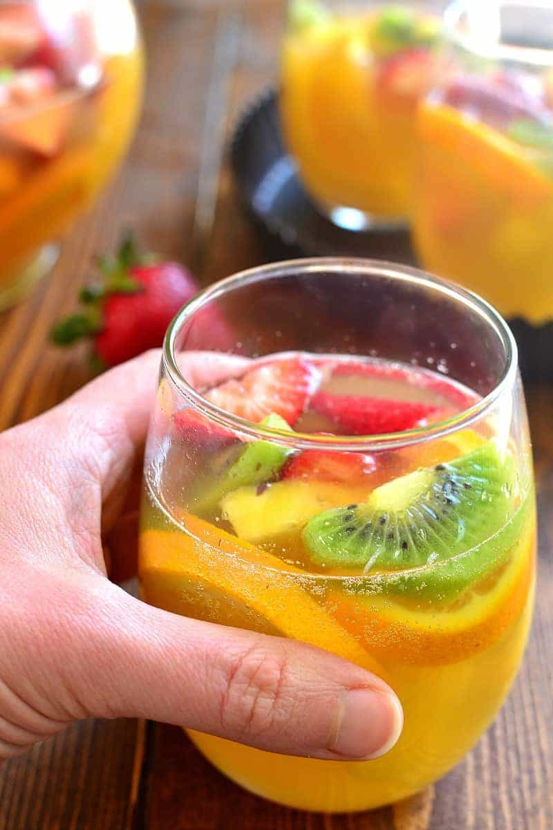 hand holding a glass of tropical fruit sangria