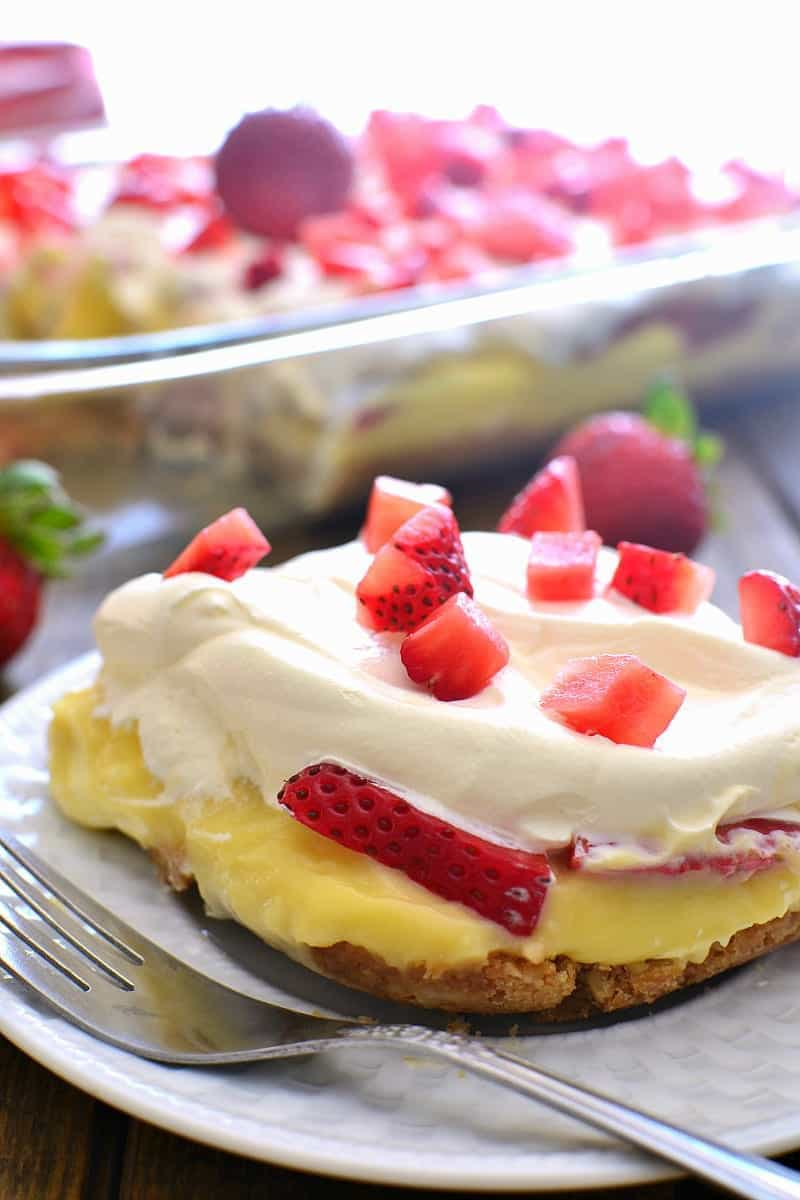 This Strawberries & Cream Lush Dessert combines a crunchy cookie crust with vanilla pudding, whipped topping, and fresh strawberries for a delicious summer treat that's guaranteed to become a favorite!