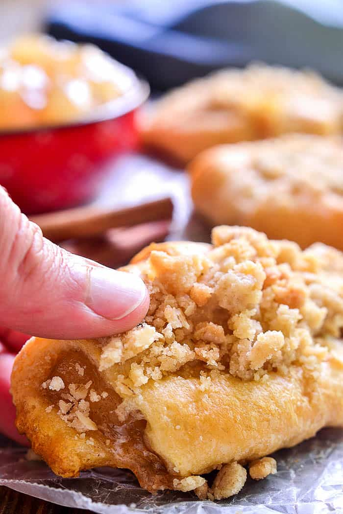 Hand grabbing an Apple Pie Crescent Roll
