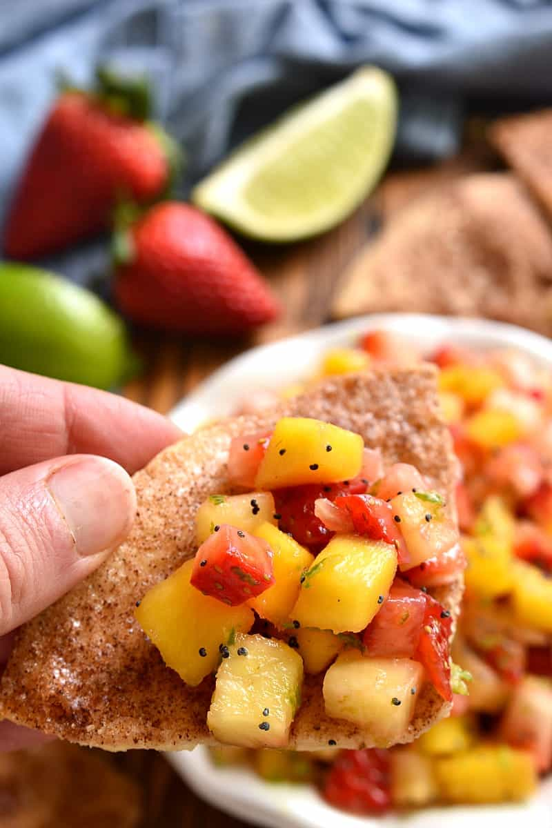 person holding a tortilla chip, dipping into a bowl of fruit salsa