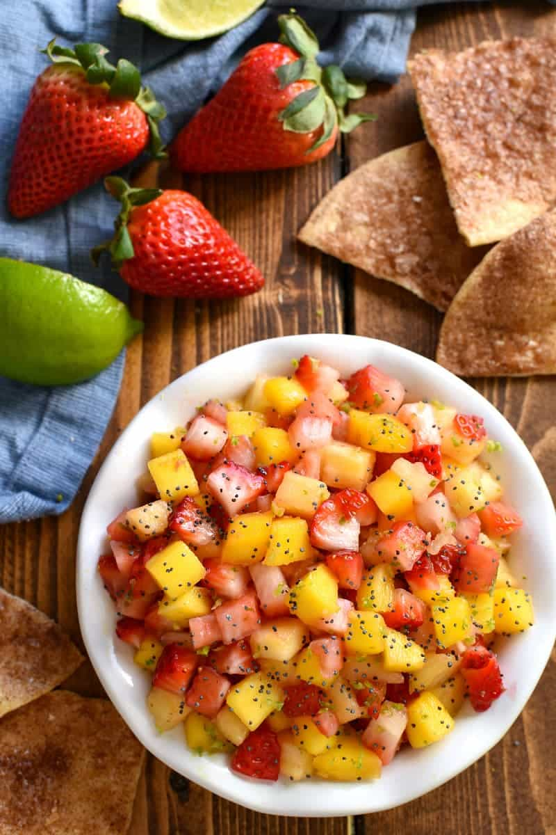 overhead image of a bowl of fruit salsa surrounded by tortilla chips and fresh strawberries