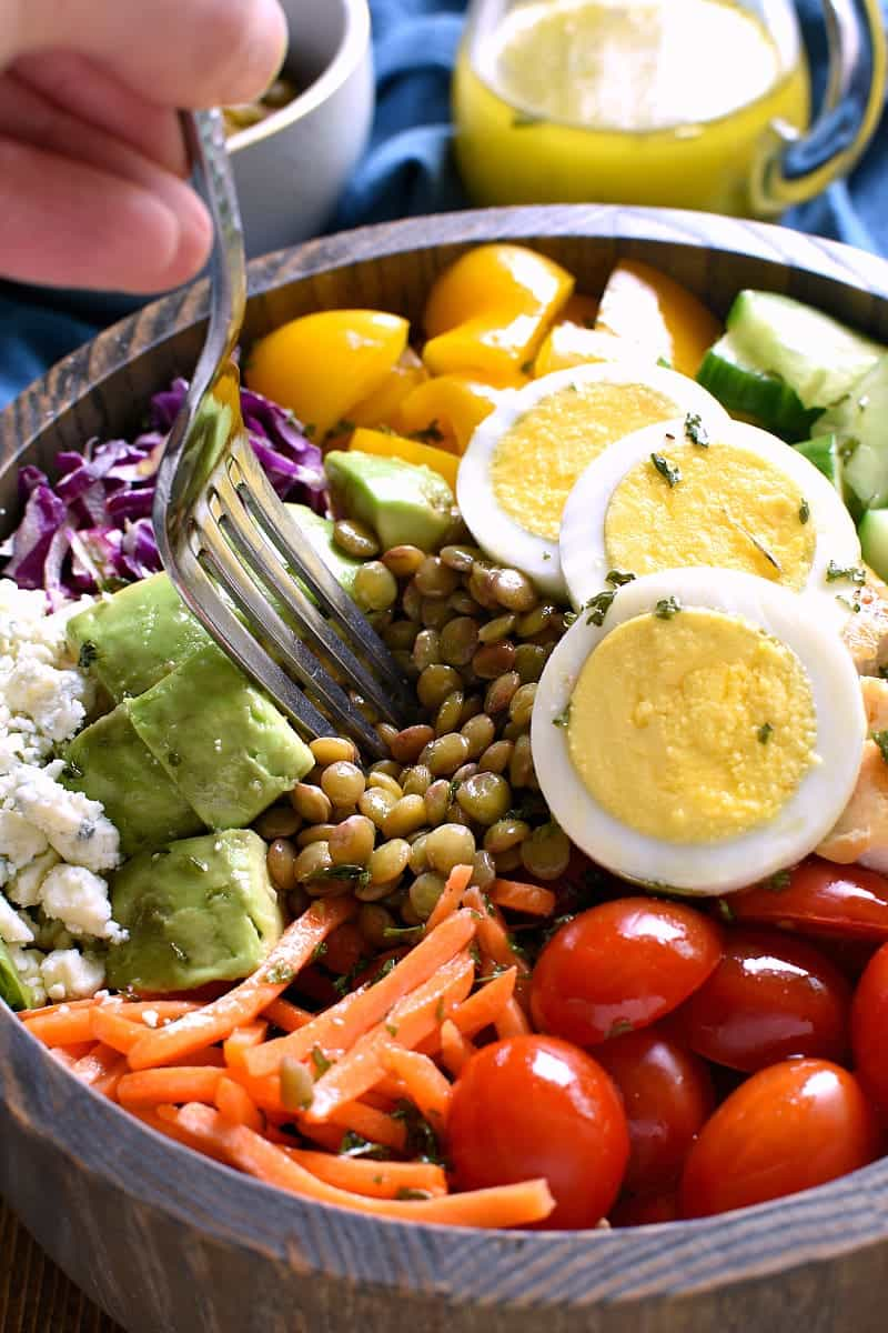 wooden bowl of protein packed salad with a fork in it