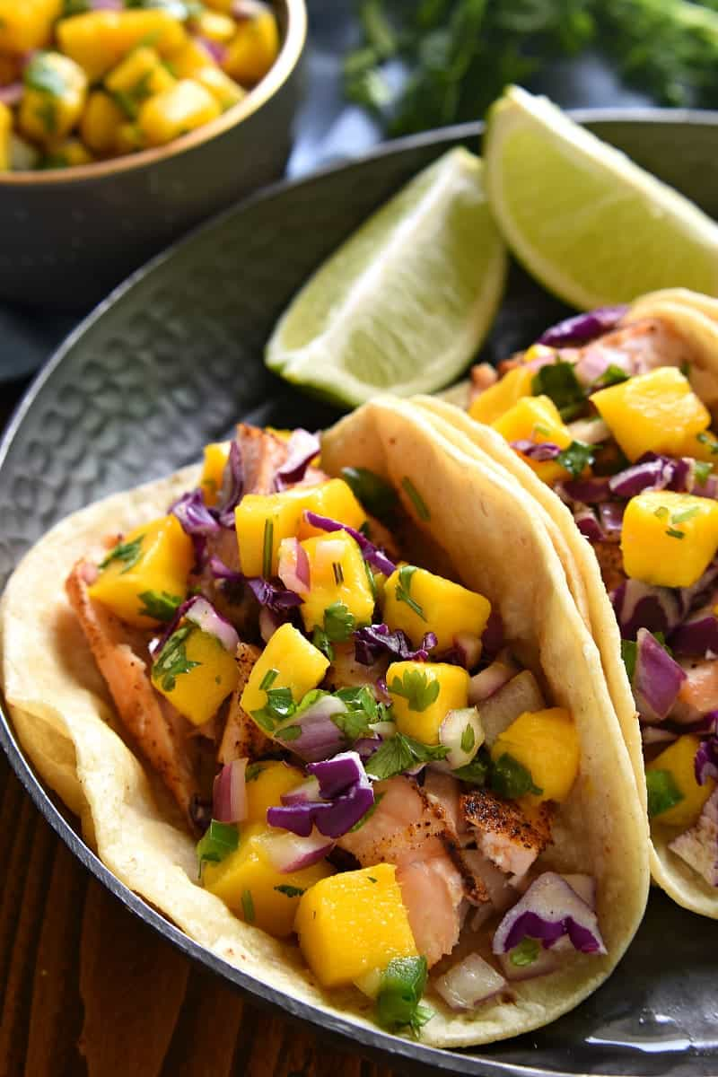 plate of salmon fish tacos topped with fresh mango salsa
