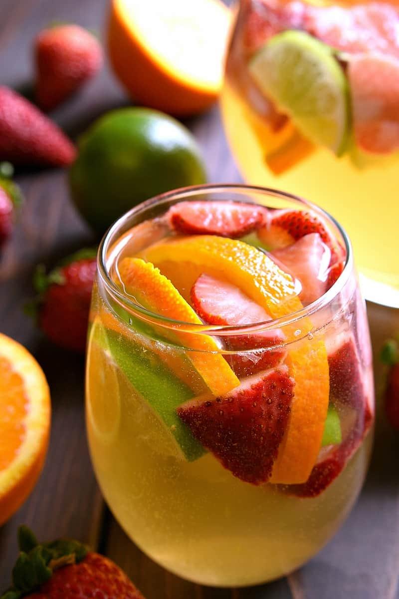 a glass of Sparkling Sangria garnished with fresh fruit slices