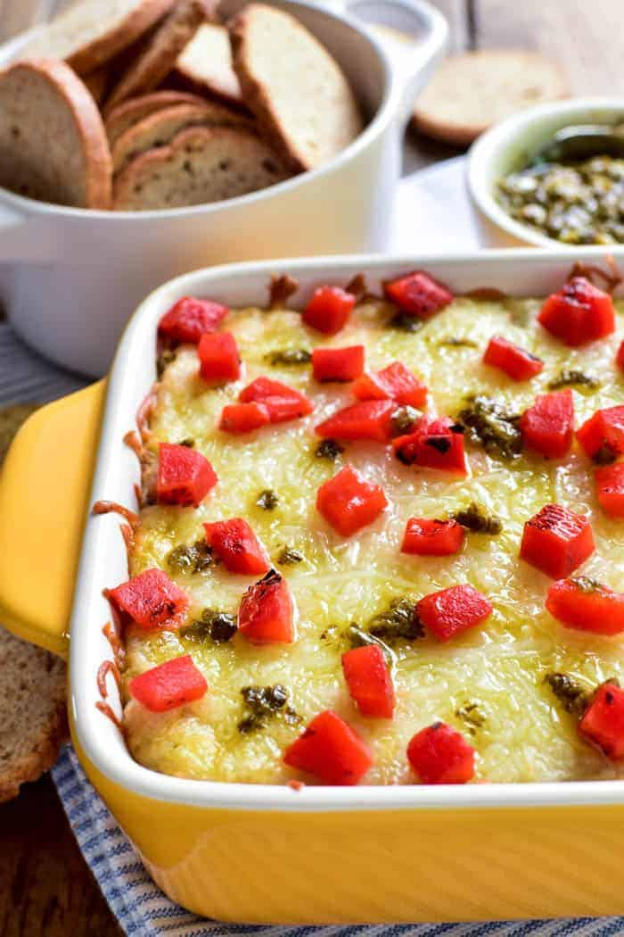 If you love pesto, you'll go crazy for this Cheesy Pesto Artichoke Dip! Loaded with gooey cheese, artichokes, pesto, and roasted red peppers, this dip is a flavor explosion in every bite. It comes together quickly with just a handful of ingredients, making it the perfect appetizer for holidays, parties, or game days. Enjoy it with crostini, crackers, or even fresh veggies. Any way you eat it, this  cheesy baked dip is guaranteed to become a new favorite!