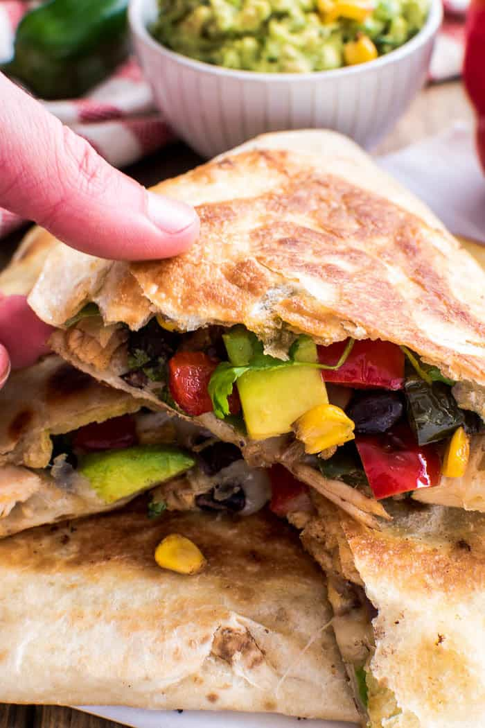 These Loaded Chicken Quesadillas have it all! Crisp tortillas stuffed with seasoned shredded chicken, bell peppers, onions, black beans, avocado, cilantro, corn, and white cheddar cheese.