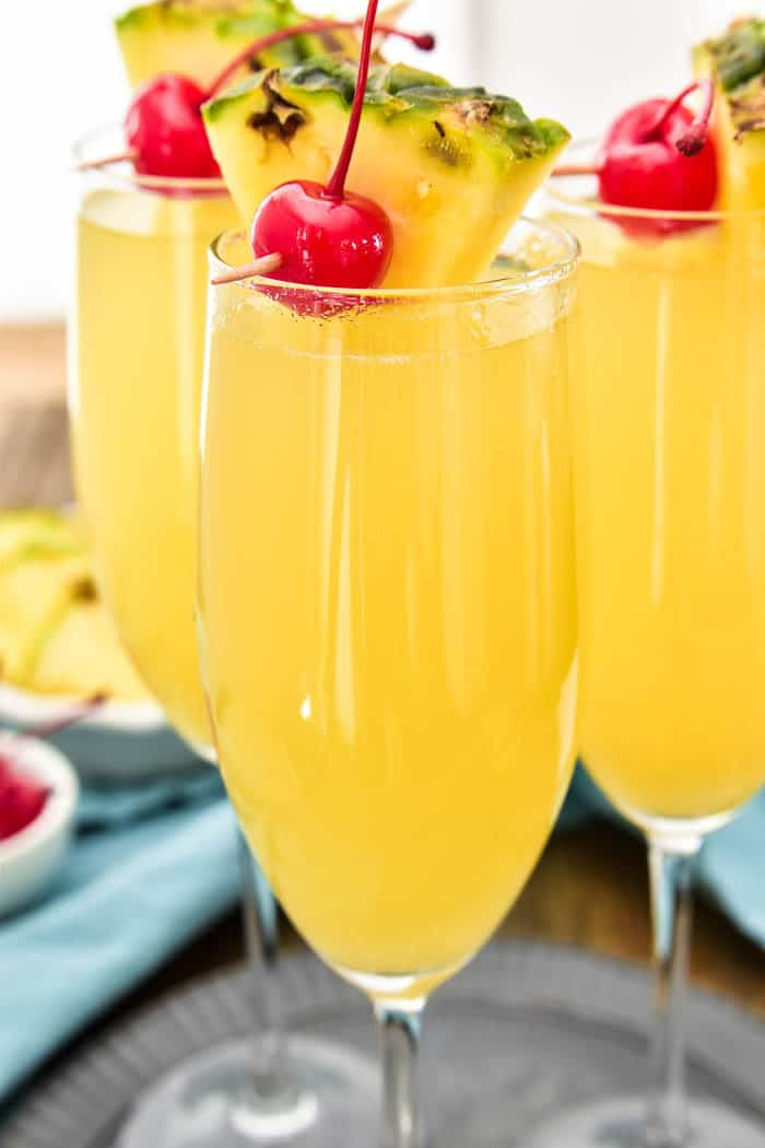 Pineapple Upside Down Mimosas are one of our favorite brunch time beverages! They combine the classic mimosa you know and love with the delicious taste of pineapple upside down cake. Made with just 3 simple ingredients, these drinks are easy to prepare and perfect for any occasion. Make your next brunch extra special with these extra special (extra yummy!) mimosas!