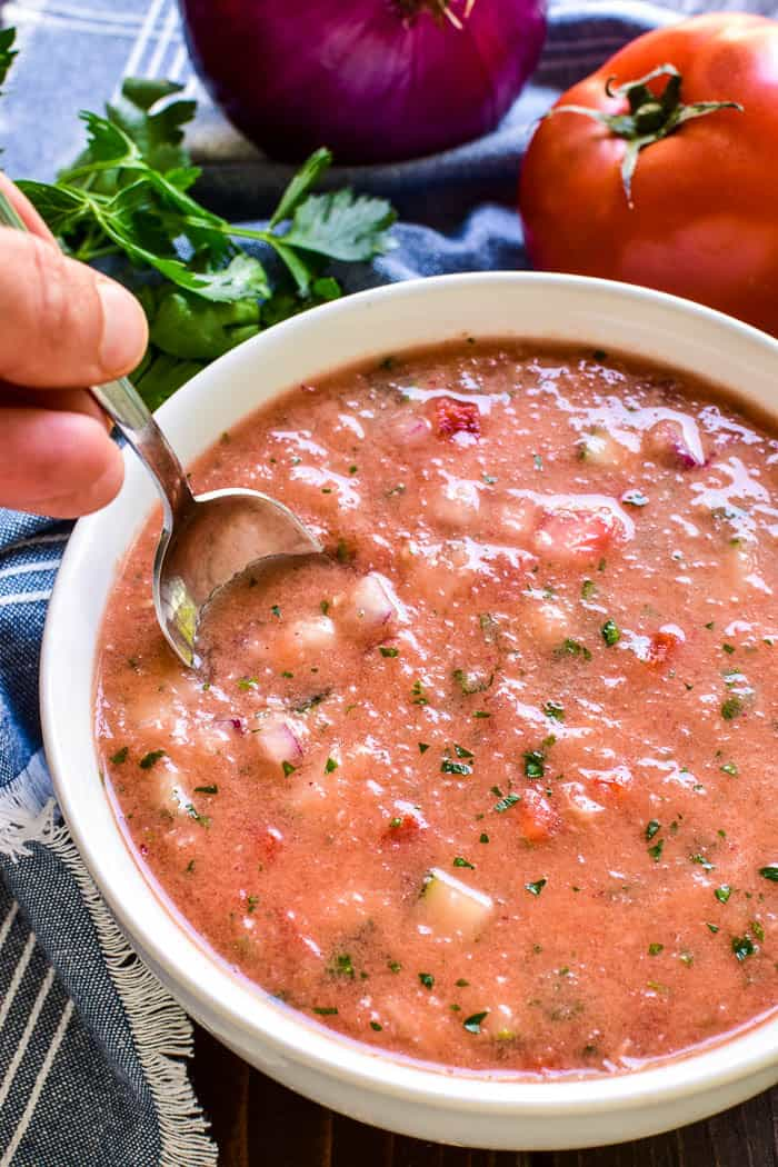 This Easy Gazpacho is the perfect way to make use of fresh garden veggies! Loaded with ripe tomatoes, cucumbers, red peppers, and onions, this chilled soup has just the right blend of flavors and textures.It makes a delicious lunch or dinner, and could also be served a light appetizer.