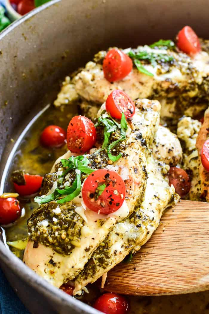 This Cheesy Pesto Stuffed Chicken is the ultimate dinner recipe! Ready in 30 minute or less, this dish is packed with flavor and so easy to make. It combines boneless, skinless chicken breasts with basil pesto, grape tomatoes, and two types of cheese. Perfect for weekday dinners or date nights in....if you're looking for an easy, delicious twist on dinner, you'll love this stuffed chicken recipe!