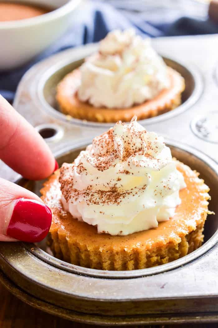 Hand reaching for Mini Pumpkin Cheesecake