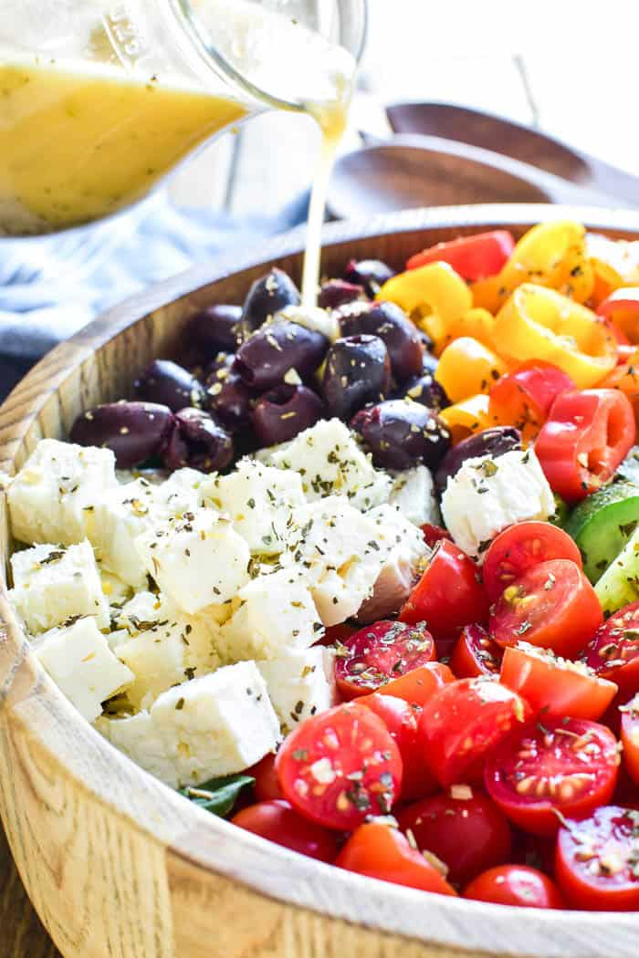 Greek Dressing pouring over salad in serving bowl
