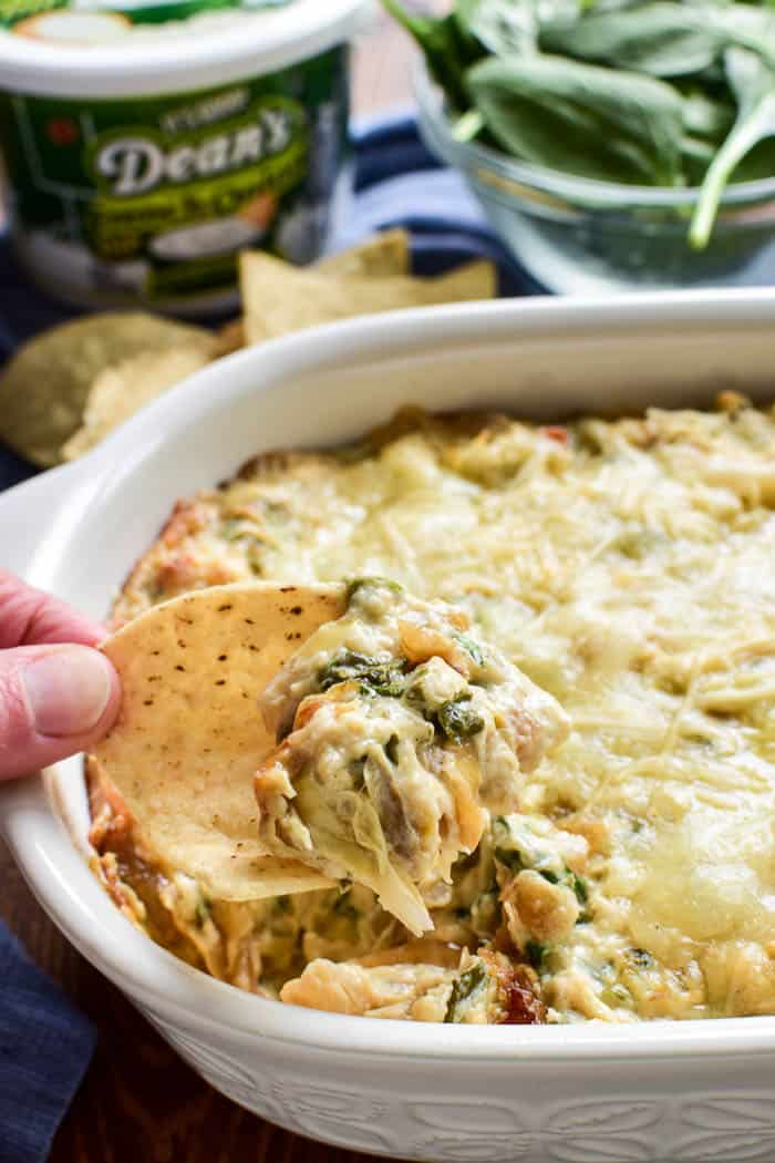 Tortilla chip dipping into French Onion Spinach Artichoke Dip