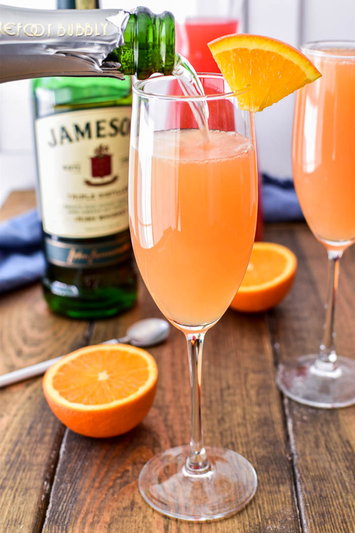 Pouring champagne into mimosa glass