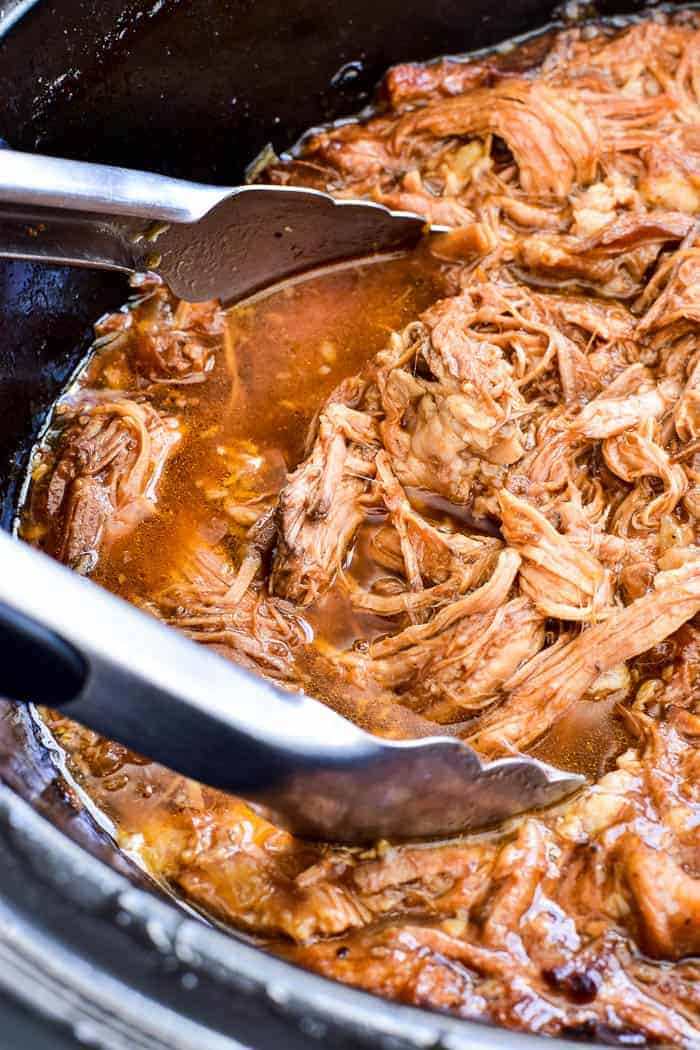 Honey Orange Pulled Pork in slow cooker with serving tongs