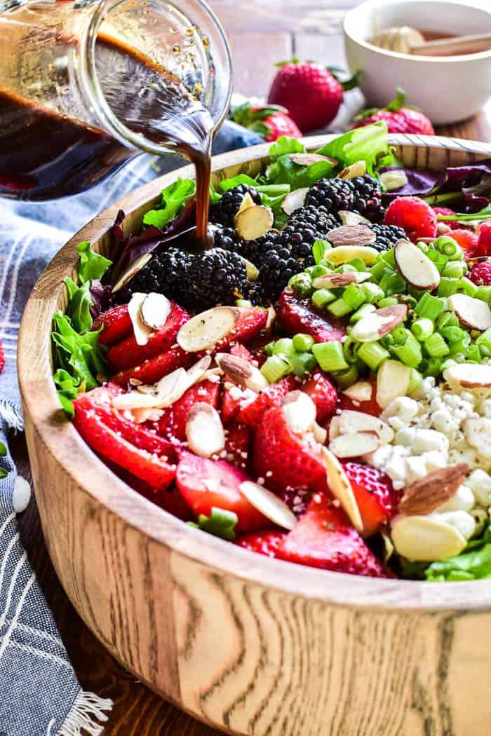 Pouring vinaigrette on Triple Berry Salad