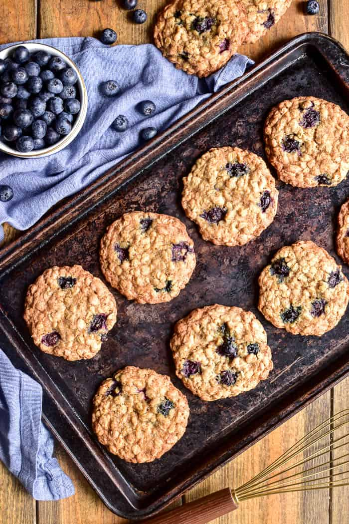 Blueberry Oatmeal Cookies on a baking sheet with fresh blueberries in the background