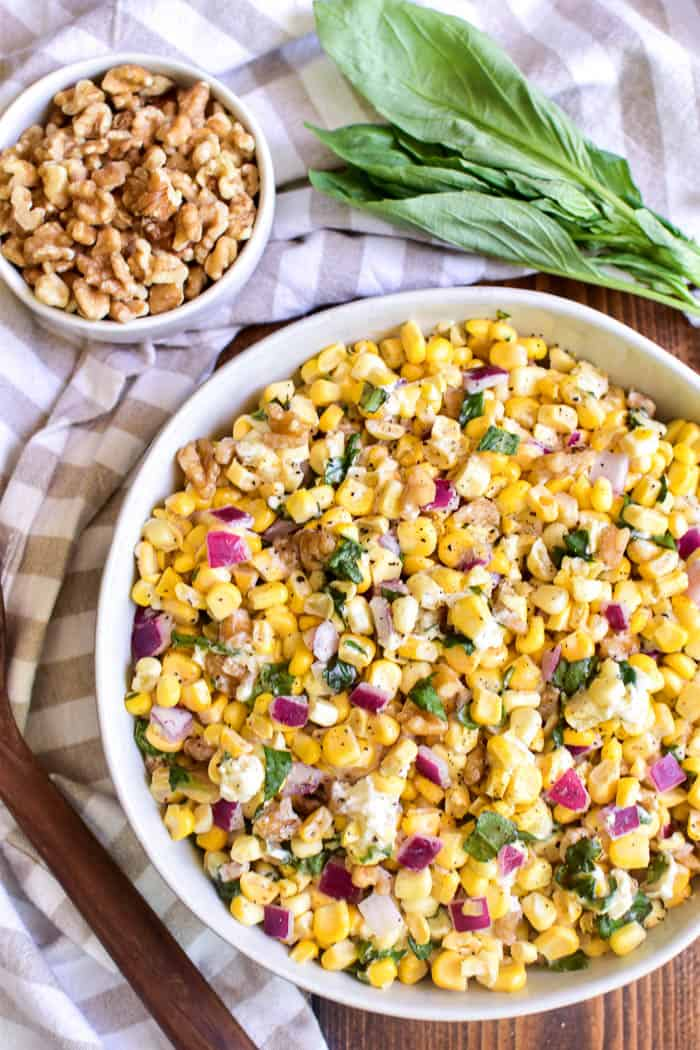 Fresh Corn Salad in a bowl with walnuts and fresh basil