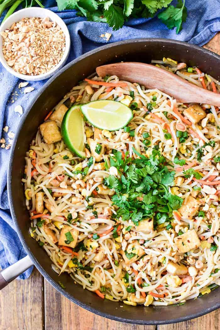 Overhead image of Pad Thai in pan with cilantro and lime wedges