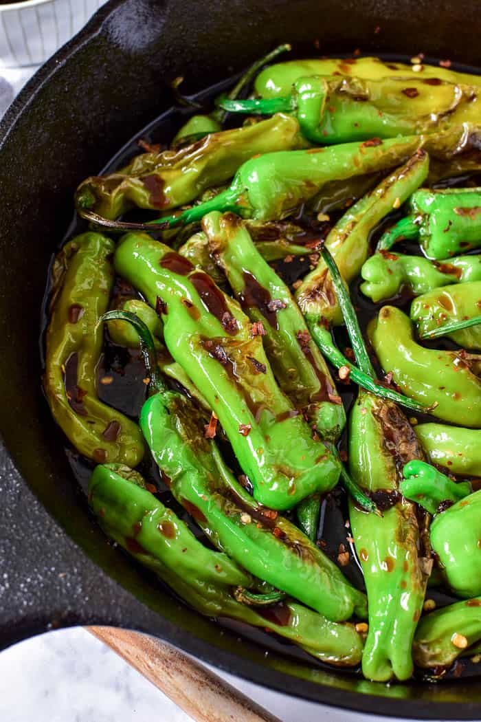 Soy Glazed Shishito Peppers in cast iron skillet