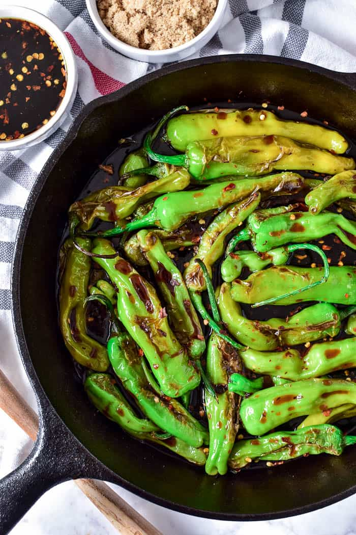 Blistered shishito peppers with soy glaze in skillet