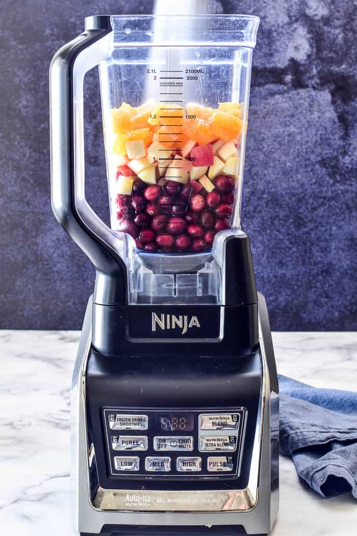 Cranberries, apples, and oranges in blender