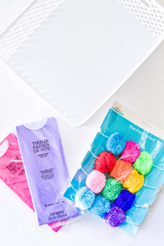 Tissue paper, pop pom garland, and basket used for gift basket