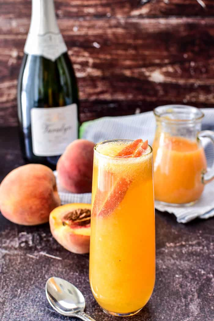 Bellini in champagne glass with fresh peaches and champagne