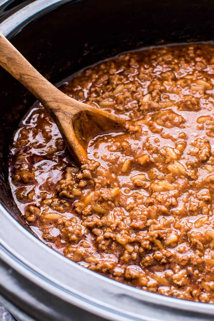 Sloppy Joes in a crock pot with a wooden serving spoon