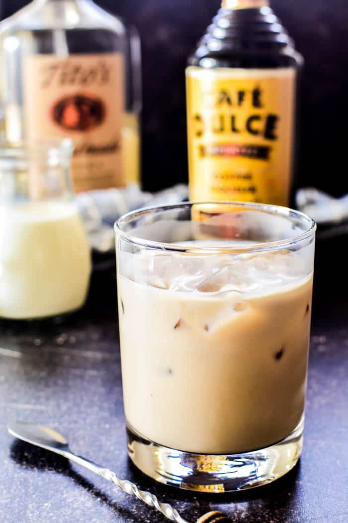 White Russian in a glass with ingredients in the background