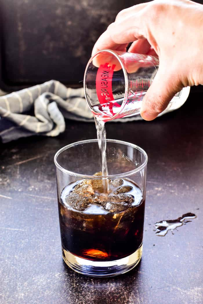 Pouring vodka into a glass filled with coffee liqueur for a White Russian