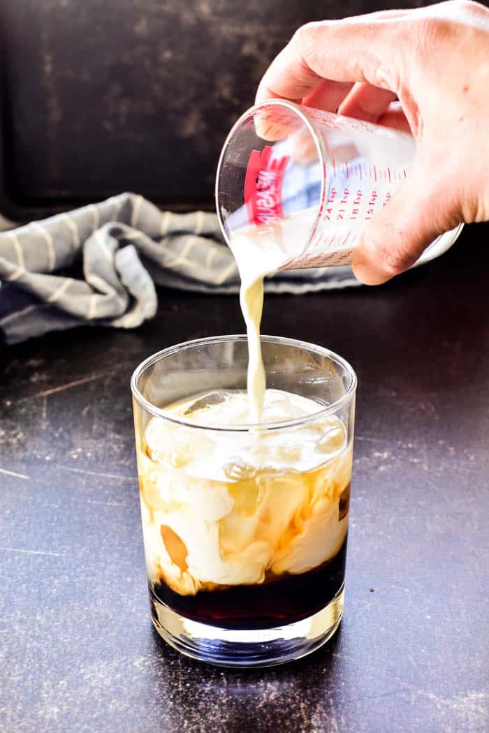 Pouring cream into a glass filled with coffee liqueur and vodka for White Russian