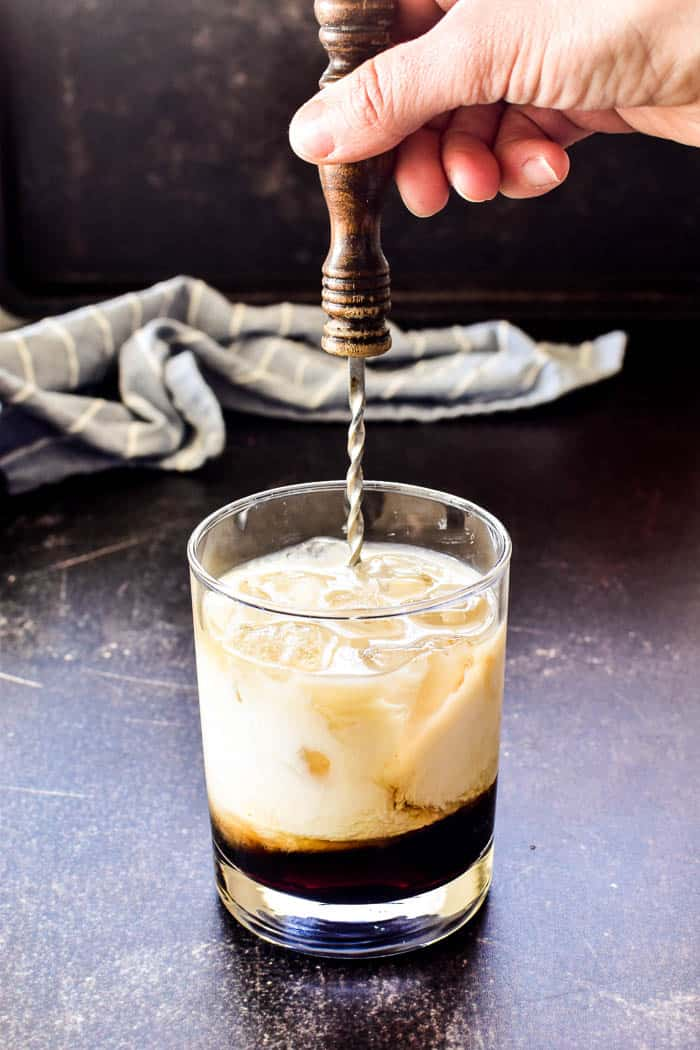 Stirring White Russian ingredients in glass with ice