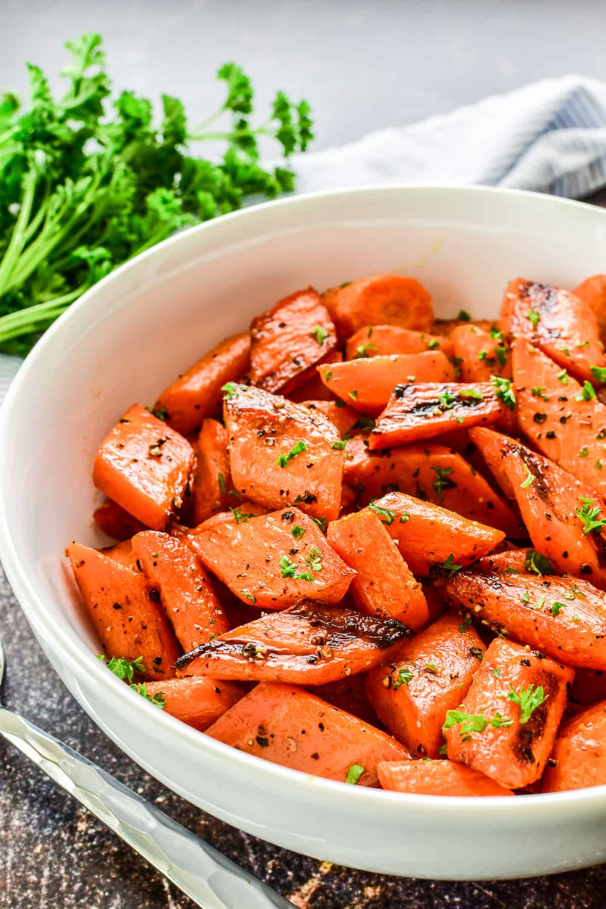 Roasted Carrots in a serving bowl with salt, pepper, and fresh parsley