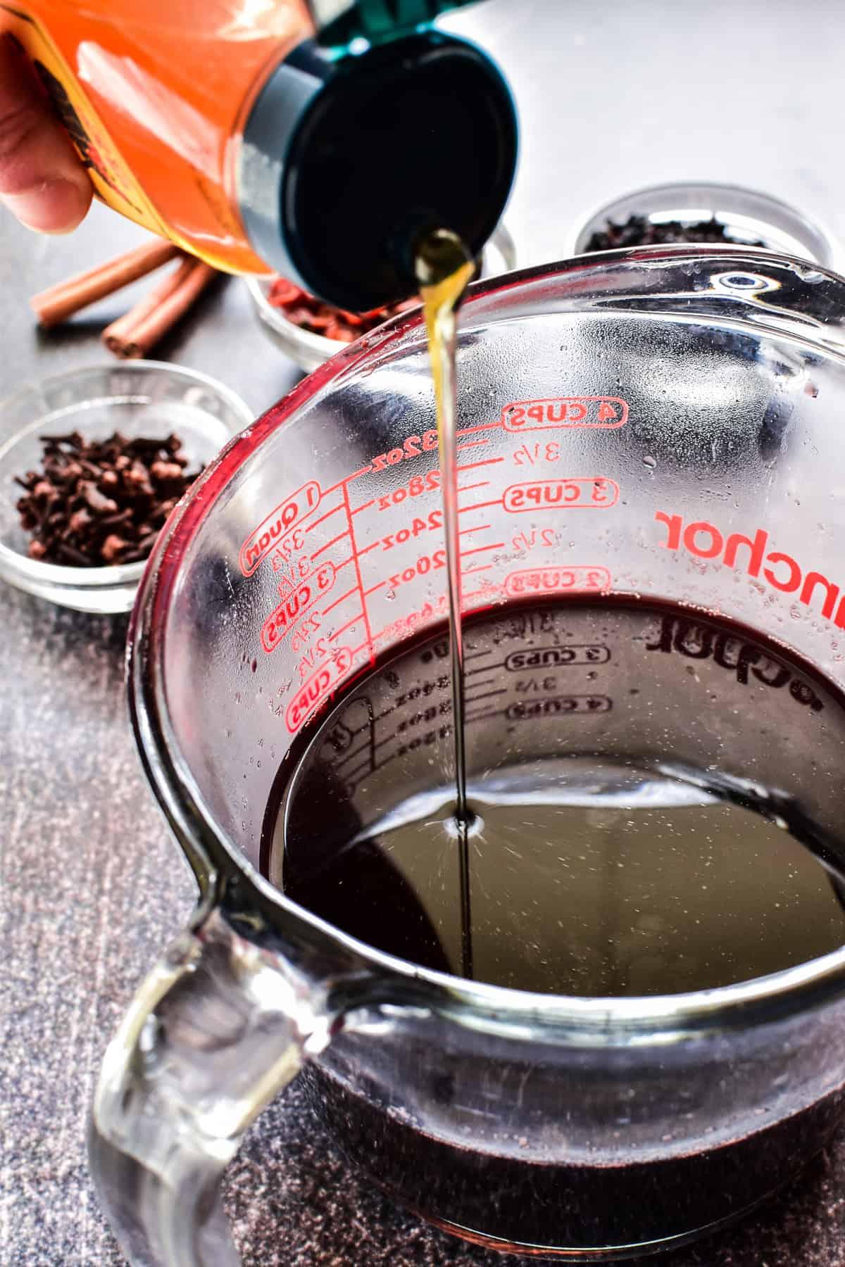 Pour shot of honey into Elderberry Syrup