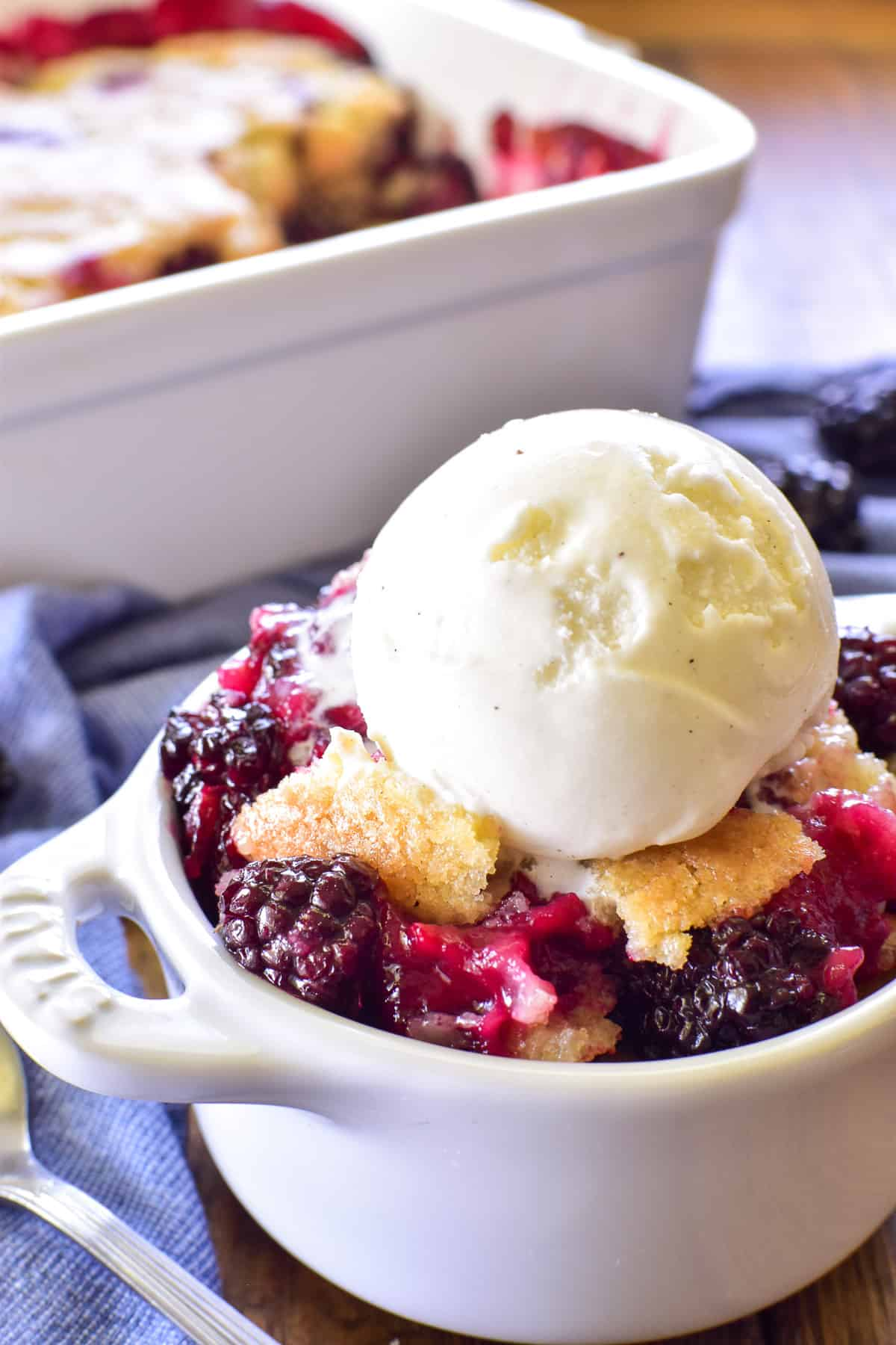 Blackberry Cobbler in a white dish with a scoop of ice cream