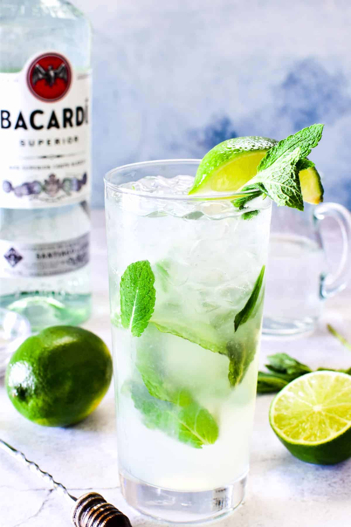 Mojito in glass with bottle of Bacardi