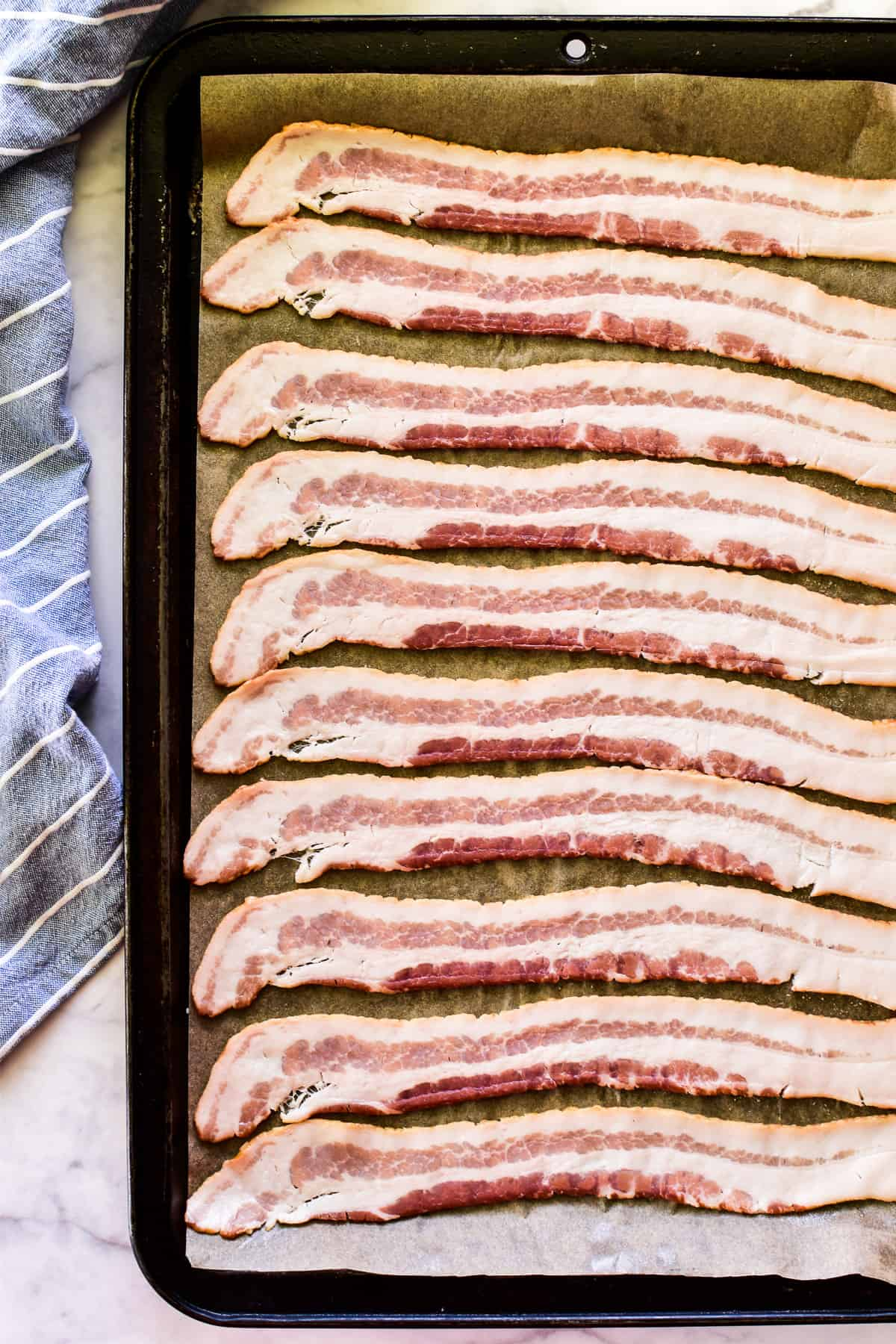 Raw bacon on baking sheet with parchment paper